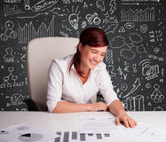 Businesswoman sitting at desk with business scheme and icons Royalty Free Stock Images