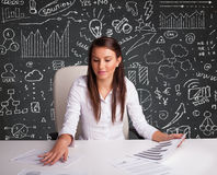 Businesswoman sitting at desk with business scheme and icons Royalty Free Stock Photo