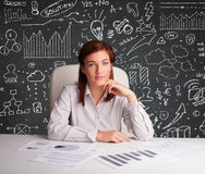 Businesswoman sitting at desk with business scheme and icons Royalty Free Stock Photos