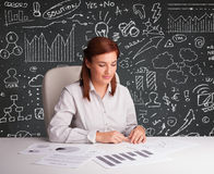 Businesswoman sitting at desk with business scheme and icons Stock Images
