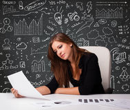 Businesswoman sitting at desk with business scheme and icons Stock Photo