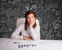Businesswoman sitting at desk with business scheme and icons Royalty Free Stock Image