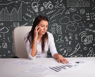 Businesswoman sitting at desk with business scheme and icons Stock Photography