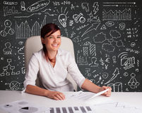 Businesswoman sitting at desk with business scheme and icons Stock Image