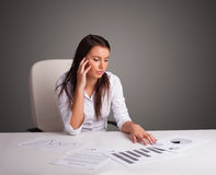 Businesswoman sitting at desk and doing paperwork Royalty Free Stock Images