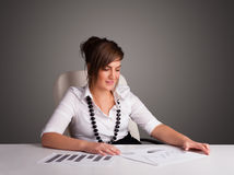 Businesswoman sitting at desk and doing paperwork Stock Images