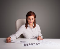 Businesswoman sitting at desk and doing paperwork Royalty Free Stock Photo