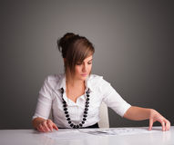 Businesswoman sitting at desk and doing paperwork Stock Photos