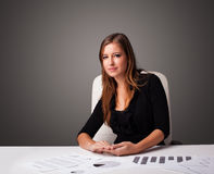 Businesswoman sitting at desk and doing paperwork Stock Image