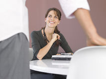 Businesswoman Sitting At Desk Looking At Male Colleague Royalty Free Stock Images