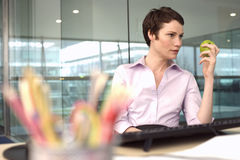 Businesswoman sitting at desk in office, holding green apple, daydreaming (differential focus) Stock Images