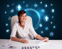 Businesswoman sitting at desk with social network icons Stock Photos
