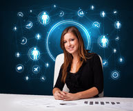 Businesswoman sitting at desk with social network icons Royalty Free Stock Photography