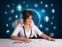 Businesswoman sitting at desk with social network icons Royalty Free Stock Photo