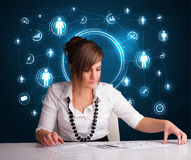 Businesswoman sitting at desk with social network icons Royalty Free Stock Photos
