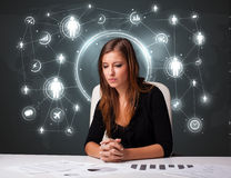 Businesswoman sitting at desk with social network icons Stock Photo