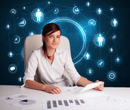 Businesswoman sitting at desk with social network icons Stock Photography