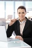 Businesswoman sitting at desk working laptop Royalty Free Stock Photography