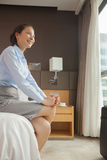Businesswoman sitting on the edge of the bed Stock Images
