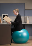 Businesswoman sitting on exercise ball. Businesswoman in headset looking at file folder while sitting on exercise ball at desk in cubicle Royalty Free Stock Image