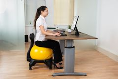 Businesswoman Sitting On Fitness Ball With Computer At Desk. Young Happy Businesswoman Using Computer While Sitting On Fitness Ball At Desk Royalty Free Stock Photo