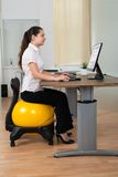 Businesswoman Sitting On Fitness Ball With Computer At Desk Stock Photo