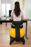 Businesswoman Sitting On Fitness Ball In Office Royalty Free Stock Images