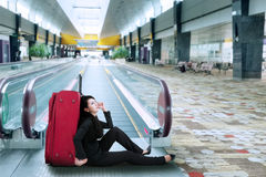 Businesswoman sitting on the floor in airport Royalty Free Stock Images