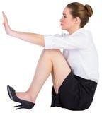 Businesswoman sitting on floor pushing Stock Photo