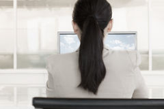 Businesswoman sitting in front of a computer with clouds and sky on the monitor Royalty Free Stock Photos