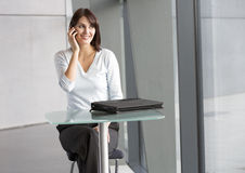 A businesswoman sitting at a glass table, talking on a mobile phone Royalty Free Stock Photo
