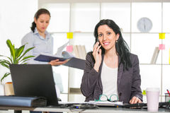 Businesswoman sitting at her desk with colleague on background Royalty Free Stock Images