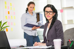Businesswoman sitting at her desk with colleague on background Stock Photo