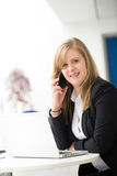 Businesswoman sitting at her desk in an office Royalty Free Stock Photography