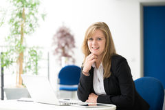 Businesswoman sitting at her desk in an office Stock Images