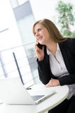 Businesswoman sitting at her desk in an office Royalty Free Stock Image