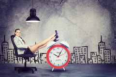 Businesswoman sitting with her feet up on alarm Stock Images