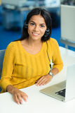 Businesswoman sitting at her workplace with headphones Royalty Free Stock Image