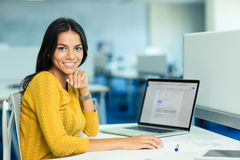Businesswoman sitting at her workplace with laptop Stock Photography