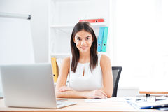 Businesswoman sitting at her workplace in office Stock Image