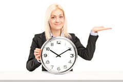 Businesswoman sitting and holding a wall clock Royalty Free Stock Images