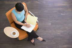 Businesswoman sitting indoors Royalty Free Stock Photo