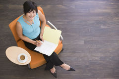 Businesswoman sitting indoors with coffee Stock Photos