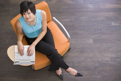 Businesswoman sitting indoors with laptop Stock Photos