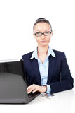Businesswoman sitting with laptop in office Royalty Free Stock Images