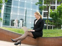 Businesswoman sitting with laptop outside the office Stock Photography