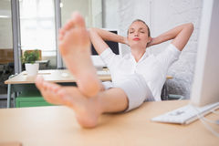Businesswoman sitting with legs crossed at ankle on desk Stock Photos