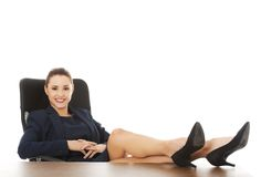 Businesswoman sitting with legs on desk Stock Photography