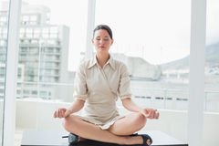 Businesswoman sitting in lotus position with eyes closed at office Stock Image