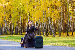 Businesswoman sitting on a luggage. Royalty Free Stock Photography
